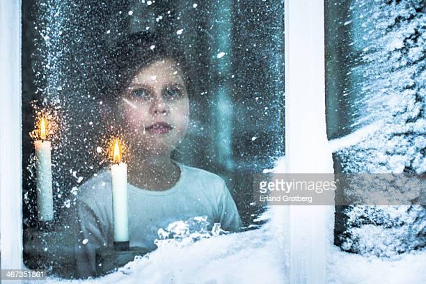 Girl in window watching snowstorm outside
