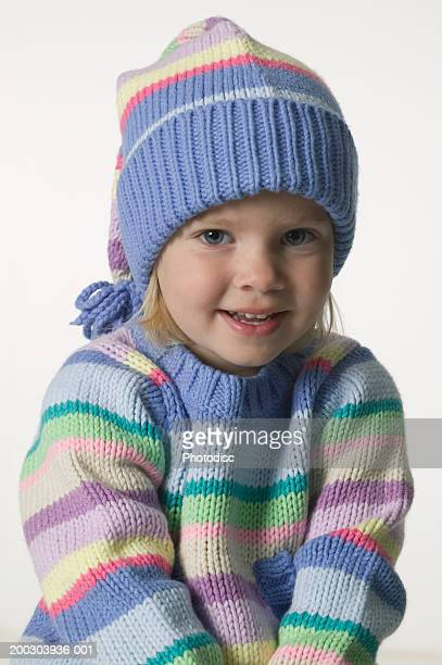 Girl (4-5) in woollen bobble hat posing in studio, portrait