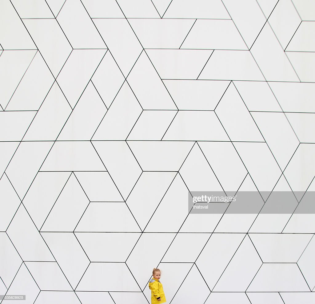 Girl (2-3) in yellow raincoat against white wall : Stock-Foto