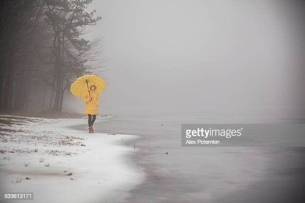 girl in yellow walks by frozen lake on cold foggy day