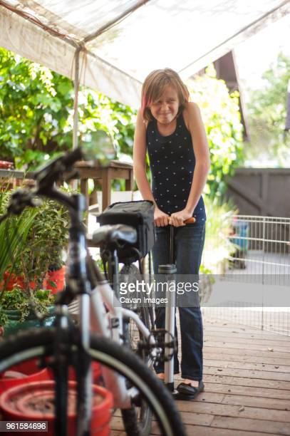 girl inflating bicycle tire at porch - air pump stock photos and pictures