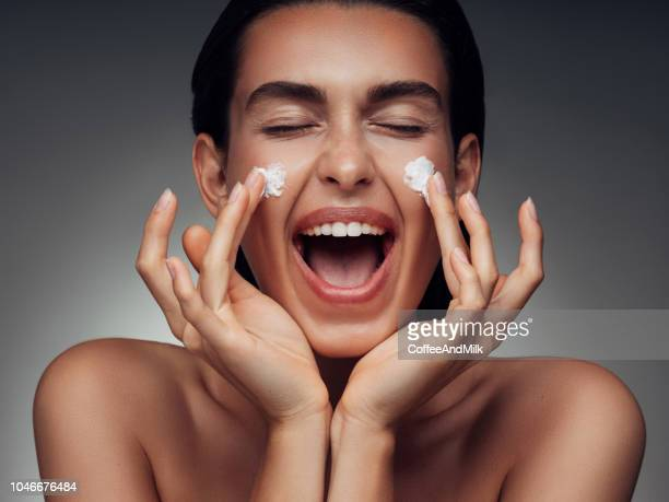 girl inflicting cream - moisturiser stock pictures, royalty-free photos & images