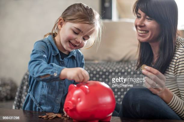 girl inserting coin from mother into red piggy bank on coffee table - piggy bank stock photos and pictures