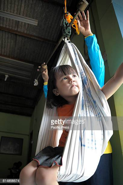 A girl inside a traditional weighing scale After being declared poliofree by World Health Organization officials in 2014 Indonesia is observing...