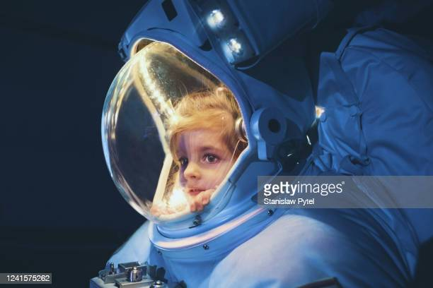 girl inside astronaut suit looking outside - space helmet stock pictures, royalty-free photos & images