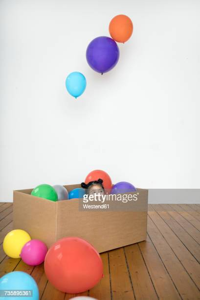 Girl inside cardboard box with balloons