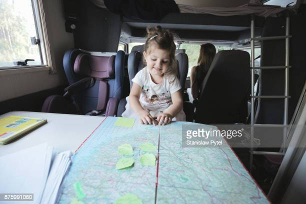 Girl inside of campervan pointing map