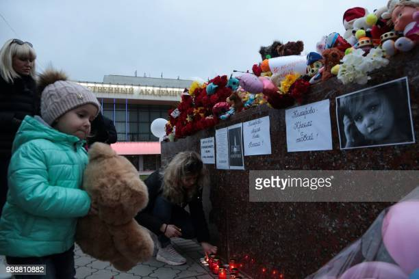 A girl is about to lay a stuffed children's toy at a makeshift memorial in tribute to the victims of a Siberian shopping mall fire in Kemerovo in...