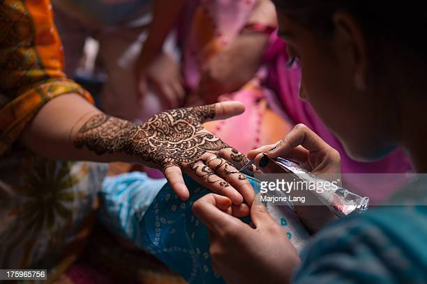 CONTENT] A girl is applying mehndi or henna on her mother's hand inside their house in old Jodhpur Rajasthan India