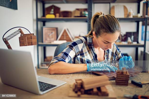 Girl is assembling a wooden clock in a small family carpenter factory