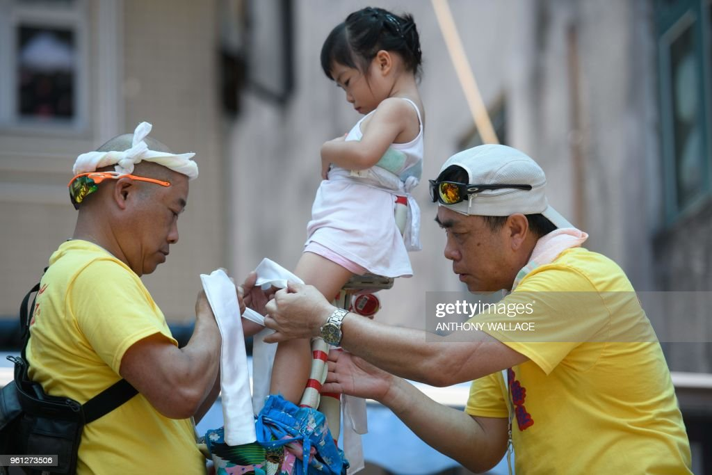 A girl is assisted by parade group members before she takes part in the annual Cheung Chau bun festival parade in Hong Kong on May 22, 2018.