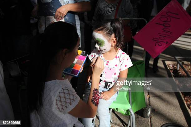 A girl is being disguised as a Catarina in the annual procession of zombies in Mexico City on November 4 2017 Hundreds dressed in rags and ghoulish...