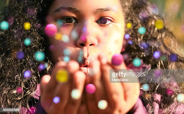 Girl is blowing colorful spangle.