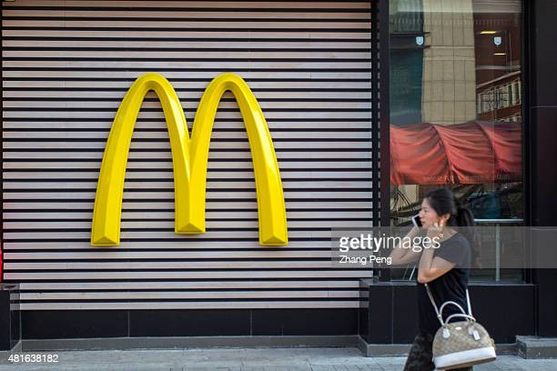 A girl is calling on a mobile phone as she walks past the huge logo on the exterior wall of a McDonalds restaurant in Shenyang downtown Huge logo of...