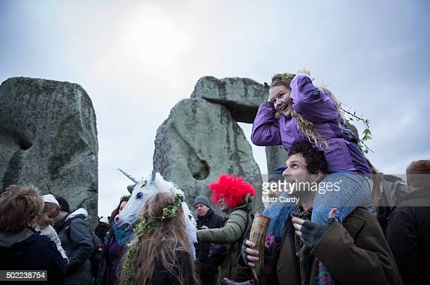 A girl is carried on a man's shoulders as druids pagans and revellers gather in the centre of Stonehenge hoping to see the sun rise as they take part...