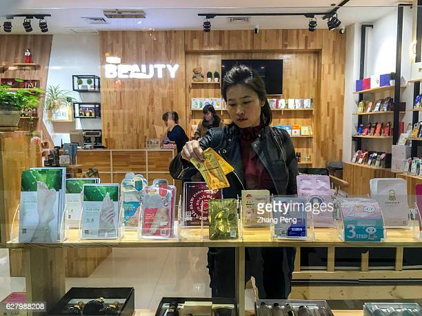 Girl is choosing facial mask in a shop selling Korean cosmetics and personal care commodities. Commercial relationship between China and South...