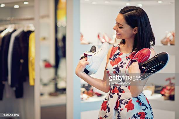Girl is choosing shoes in a boutique and make fun