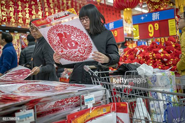 A girl is choosing traditional papercut window decoration in a Walmart store To welcome Chinese traditional Spring Festival at the end of January...