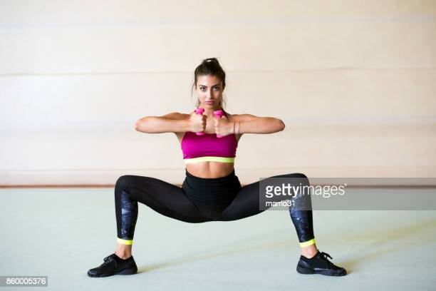 girl is doing exercise with dumbbells - doing the splits stock photos and pictures