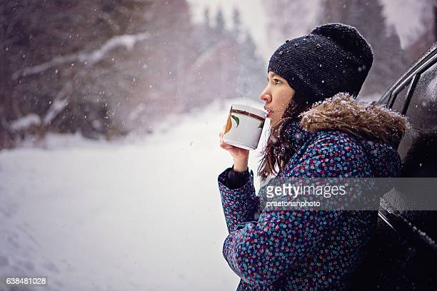 Girl is drinking hot tea in the snowy forest