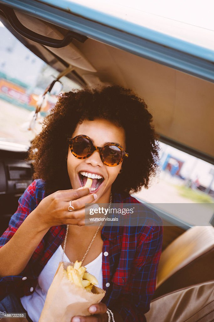 Girl is eating french fries : Stock Photo