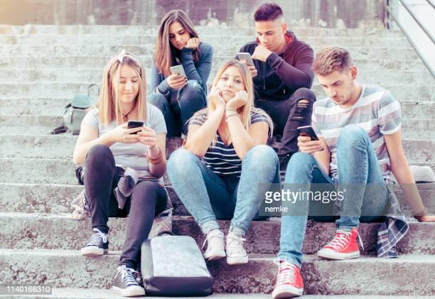 女の子は完全に一人で感じている、彼女のスマートフォンに取りつかれた友人に無視 - 囲む ストックフォトと画像