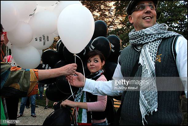 Girl is giving balloons on a pro palestinian demnstration, in budapest.