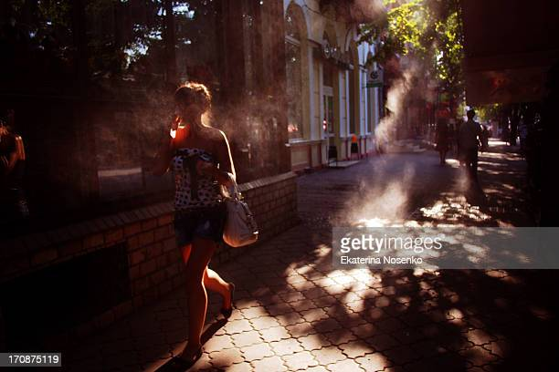 Girl is having a cold drink while walking at the Derebasovskaya street on a very hot summer day in Odessa, Ukraine.