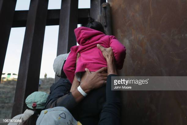 A girl is hoisted by fellow members of the migrant caravan over the USMexico border fence on December 2 2018 from Tijuana Mexico Numerous members of...