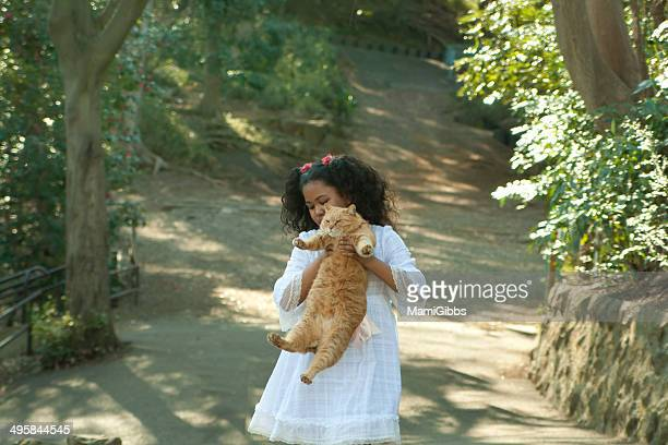 Girl is holding a cat at the forest
