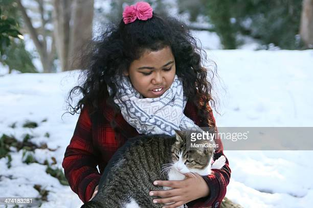 Girl is holding a cat at the snow forest