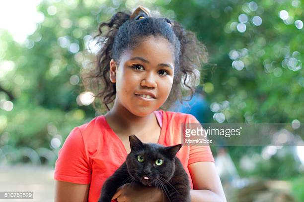 girl is holding a funny black cat - funny black girl ストックフォトと画像