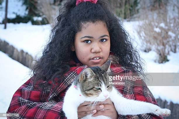 Girl is holding cat at the snow park