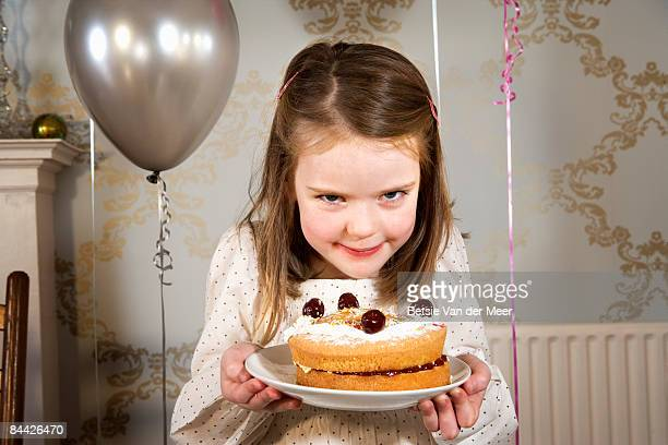 Girl is holding her selfmade birthday cake.