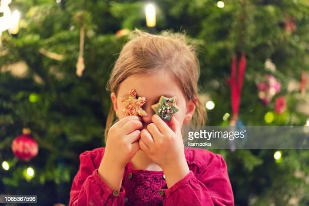 mädchen hält sterne cookies vor ihren augen in der weihnachtszeit - advent stock-fotos und bilder