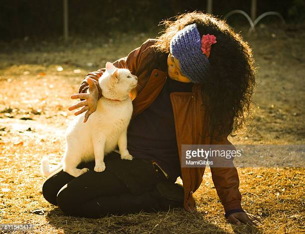 Girl is hugging cat in sunset