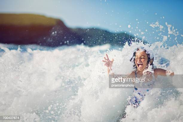 Girl is jumping and playing in the ocean in the big waves