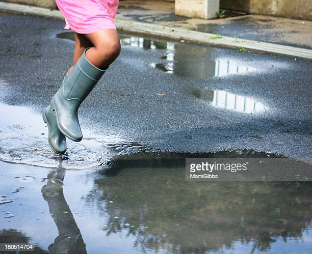 Girl is jumping in the puddle