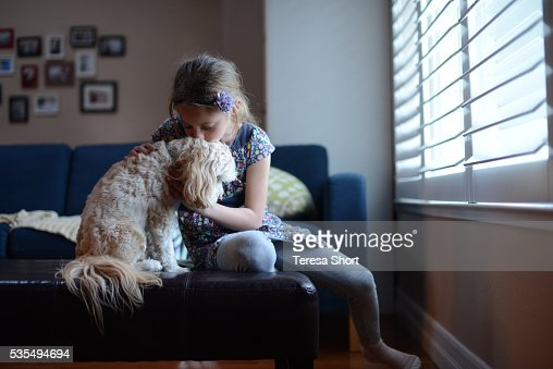 A girl is kissing a small dog on the head