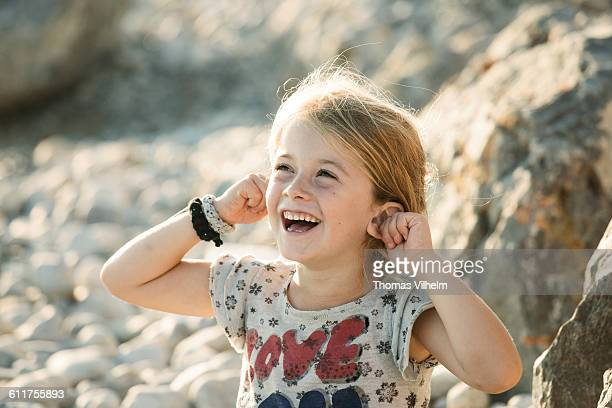 Girl is laughing and pulls her ears