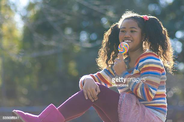 girl is licking the candy on the grass - mamigibbs stock photos and pictures