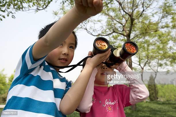 A girl is looking through binoculars.
