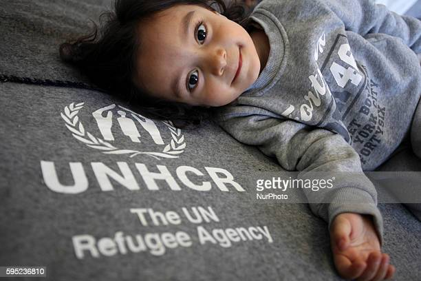 A girl is lying on a UNHCR blanket Refugees and immigrants find shelter at the former Athens International Airport Elliniko in Athens on Mar 19 2016...
