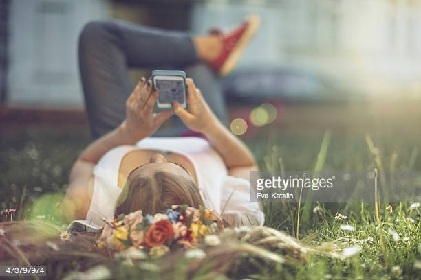 Girl is lying on back and surfing on the net