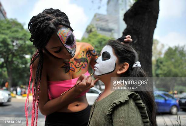 A girl is made up as Catrina during the Catrinas Parade along Reforma Avenue in Mexico City on October 26 2019 Mexicans get ready to celebrate the...