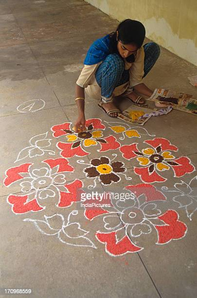 A girl is making a rangoli in her house during a festive season India