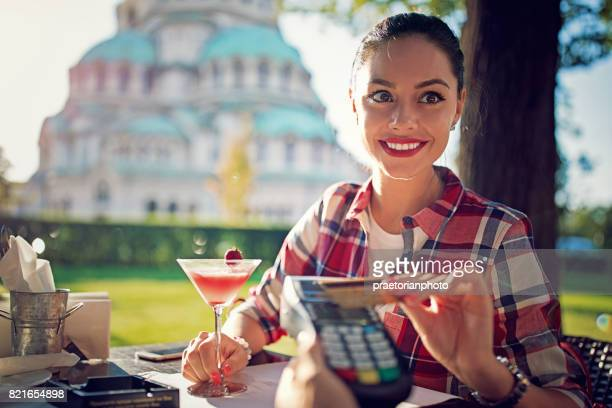 Girl is paying her cocktail using contactless credit card