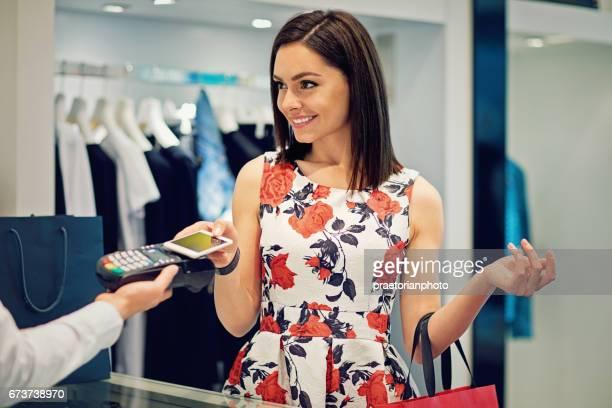 Meisje is betalen met behulp van haar mobiele telefoon in het winkelcentrum