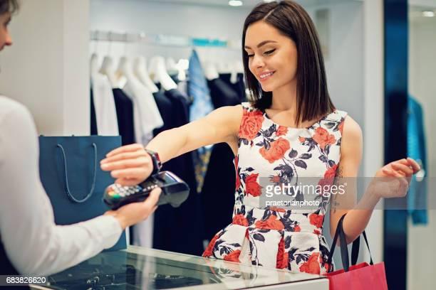 女の子がショッピング モールで彼女のスマートな腕時計を使用して支払うこと