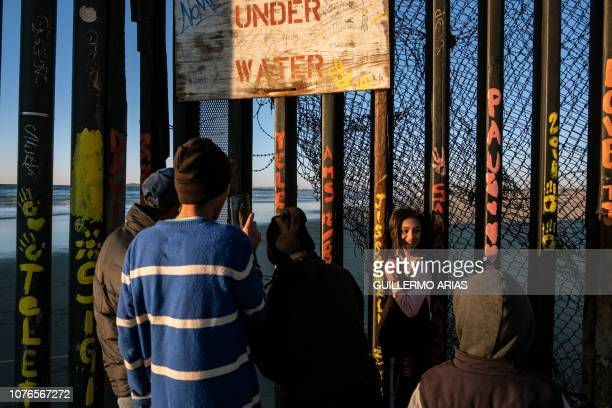 A girl is photographed by family members between the US Mexico border fence bars in Playas de Tijuana Baja California state Mexico on January 2 2018...